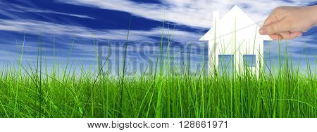 Concept or conceptual white paper house held in hand by a man in a green summer grass over a blue sky background with clouds banner