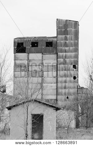 Facade building an abandoned factory overgrown with grass and trees on wasteland.