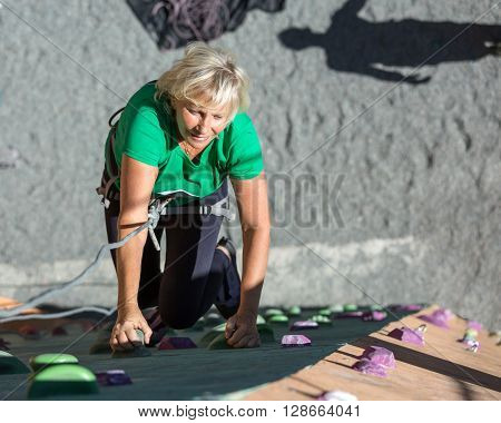 Elderly Female Makes Hard Move on Outdoor Climbing Wall Sporty Clothing on Fitness Training Shadow of Her Belaying Partner on Background