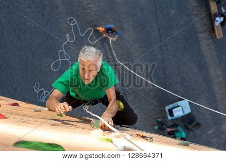 Aged Climber Makes Hard Move on Outdoor Vertical Gym Sporty Clothing Intense Emotional Face Belaying Partner on Background