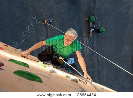 Aged Climber Makes Hard Move on Outdoor Vertical Gym Sporty Clothing Intense Emotional Face other Team Members on Background