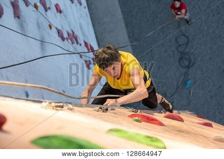 Elderly Female Demonstrates Excellent Physical and Mental Abilities Ascending Vertical Climbing Wall Belaying Partner Staying Below on Remote Ground