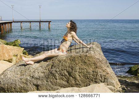 Young European woman with brown hair in bikini sits on big stone near sea.