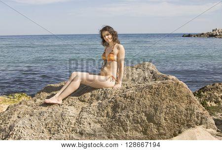 Young European woman in bikini with brown hair sit on big stone on seashore