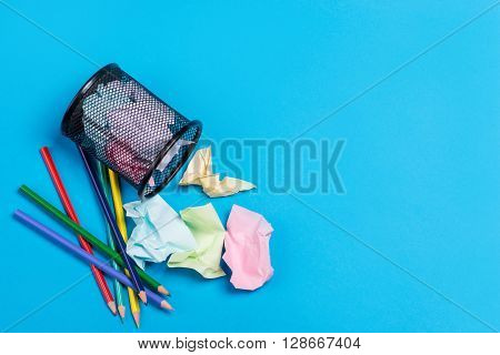 Office Trash Bin With Pencils And Crumpled Color Paper Over The Blue Background