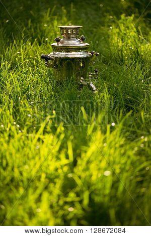Rustic samovar on the fresh summer lawn. Copyspace.