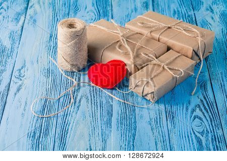 Present Box Packed In Kraft Paper On Blue Wooden Table