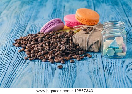 Colored french macaroons on wooden table with gift