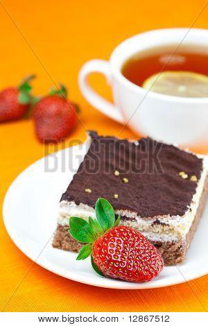Lemon Tea, Cake And Strawberries Lying On The Orange Fabric