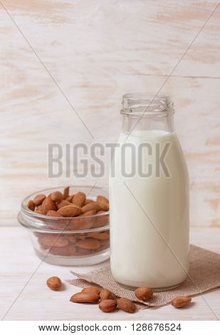 almond milk in a glass bottle almonds on a old wooden background