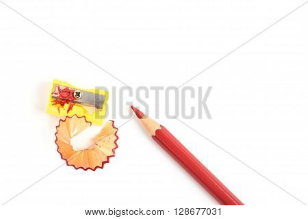 Sharp red colored pencil with yellow sharpener and shavings - isolated object on white background