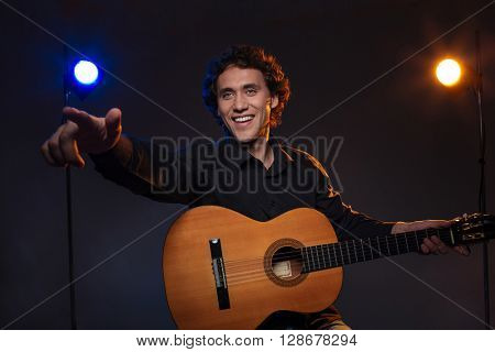 Happy man holding guitar and pointing finger on somebody over dark background