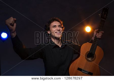 Happy man with a guitar gets applause over dark background