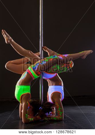 Pole dance. Two flexible girls posing while doing handstand