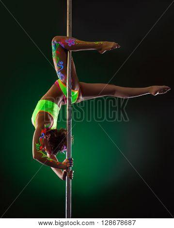 Studio image of slender girl hanging upside down on pylon