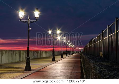 Nizhneimeretinskaya embankment with glowing lanterns and bicycle path Sochi Russia HDR processing