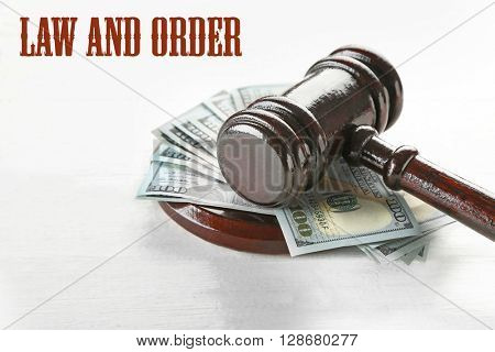 Gavel with money on wooden background. Law and order concept