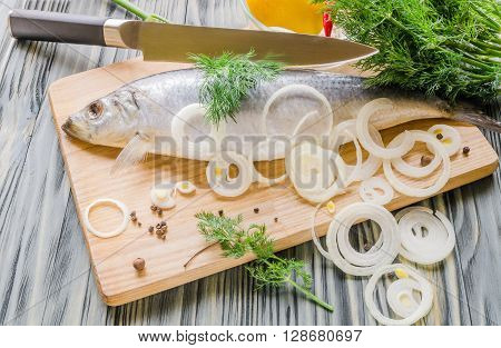herring fish on a cutting board with a knife with dill lemon and vegetables