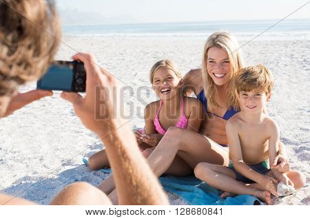 Father clicking picture of family at beach. Family posing for a photo during summer vacation. Cheerful mother sitting with son and daughter at beach for photo.