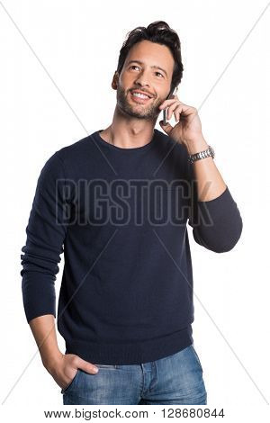 Young handsome man talking over phone and looking away. Young man using smartphone isolated on white background. Smiling guy at cellphone against a white background and looking up.