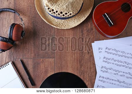 Guitar, headphones, music sheets and straw hat on wooden surface, top view