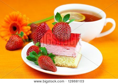 Gerbera, Lemon Tea, Cake And Strawberries Lying On The Orange Fabric