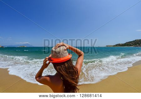 Young girl holding her hat on sandy beach in a windy day Greece Sithonia