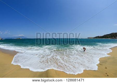 Young girl walking along the golden sandy beach and playing in the waves with footprints in the foreground and mountain Athos in background Greece Sithonia