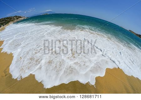 Golden sandy beach with white waves in a sunny windy summer day fisheye seascape with mountain Athos in background Greece Sithonia