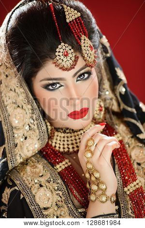 Portrait of a beautiful female model in tradition asian indian bridal costume with heavy jewellery and makeup