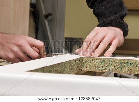 Processing kitchen countertop before installing, and the hands of a carpenter's hand tools