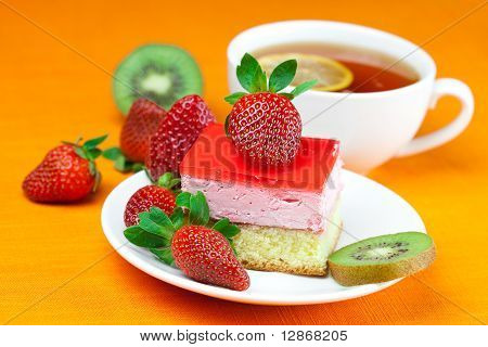 Lemon Tea, Kiwi,cake And Strawberries Lying On The Orange Fabric