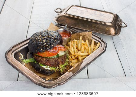 Black burger with fries and ketchup, served in a metal container with a patina on white wood table