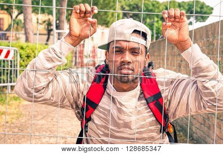African man refugee clinging to metal net looking camera in pensive mood - Young afro migrant male holding border mesh - Black guy behind bars - Unhappiness cultural and political barriers concept