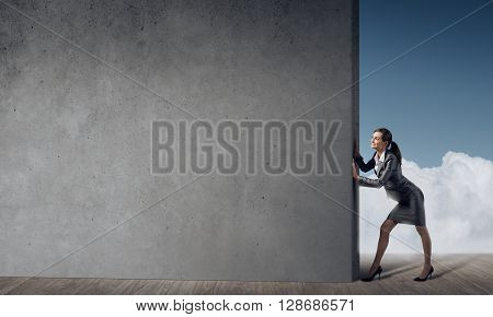 Young businesswoman making effort to move cement wall