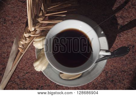 cup of tea on a saucer chocolate candy and decorative weaving straw