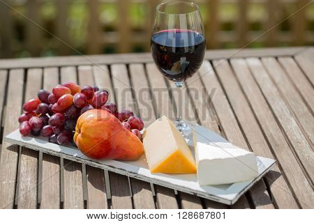 glass of red wine, with chees and grapes, in the garden