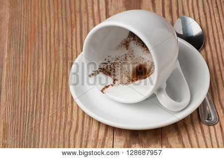 Drunk cup of strong coffee with coffee spent grounds on saucer and spoon on rustic wooden table, focused on coffee grounds, low angle view with place for text