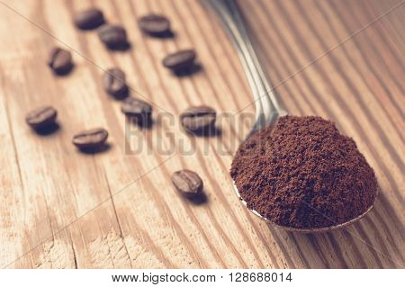 Spoon full of ground coffee and scattered coffee beans on rustic wooden board, shallow depth of field focused on ground coffee, vintage filtered