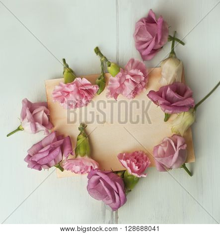 Photo of tender pink flowers (carnations and eustomas) forming frame around sheet of aged paper with copyspace both on old page and on teal blue wooden board texture behind it; slightly toned