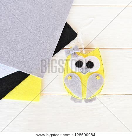 Cute felt owl toy. Grey, yellow, black, white felt. White background. Top view