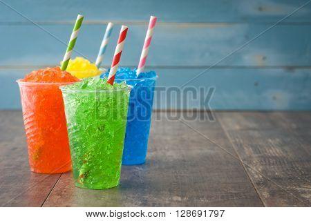 Fresh colorful summer slushies on rustic wood