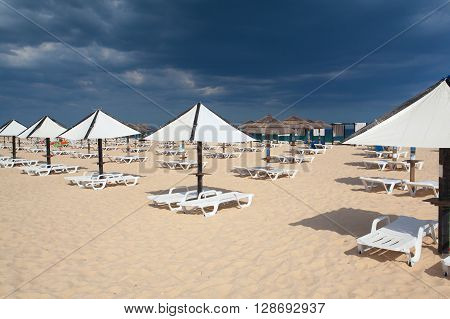 Different parasols and sun loungers on the beach on Tavira island before heavy storm. Algarve. Portugal