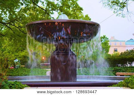 Large water fountain with running water taken in a lush green garden