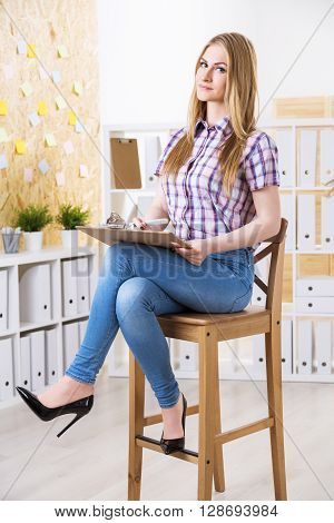 Businesswoman with document in hands sitting on wooden stool in office