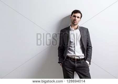 Businessperson with hands in pockets isolated on white wall. Mock up