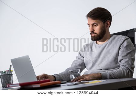 Bearded caucasian businessman working on laptop at office desk with glass of water and office tools. Sideview