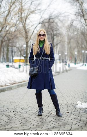 Young blonde woman in a blue coat posing on a background of a winter park
