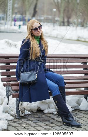 Young blonde woman in a blue coat sitting on a bench in winter park