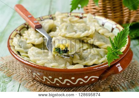 Dumplings with cheese and nettles in a traditional ceramic plate. Russian traditional cuisine